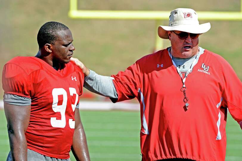 Lamar head coach Ray Woodard talks to Jesse Dickson before the Lamar University football scrimmage.