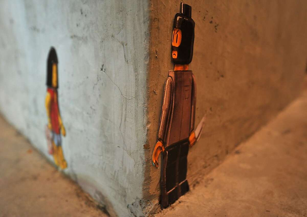 Lying in wait: On a restaurant wall in Kuala Lumpur, a paper cut-out of a street mural originally created by Lithuanian artist Ernest Zacharevic shows a knife-wielding LEGO robber waiting to mug a LEGO woman carrying a Chanel bag. The original artwork was whitewashed by Malaysian authorities, who didn't appreciate the attention to the nation's crime problem. Since then the image has gone viral, with versions popping up across the country and earning their creator comparisons to UK graffiti artist Banksy.