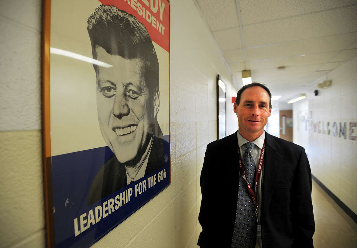 Principal Sean Smyth stands by a John F. Kennedy campaign poster, one of the many Kennedy items on display at John F. Kennedy School in Milford, Conn. on Thursday, November 21, 2013.