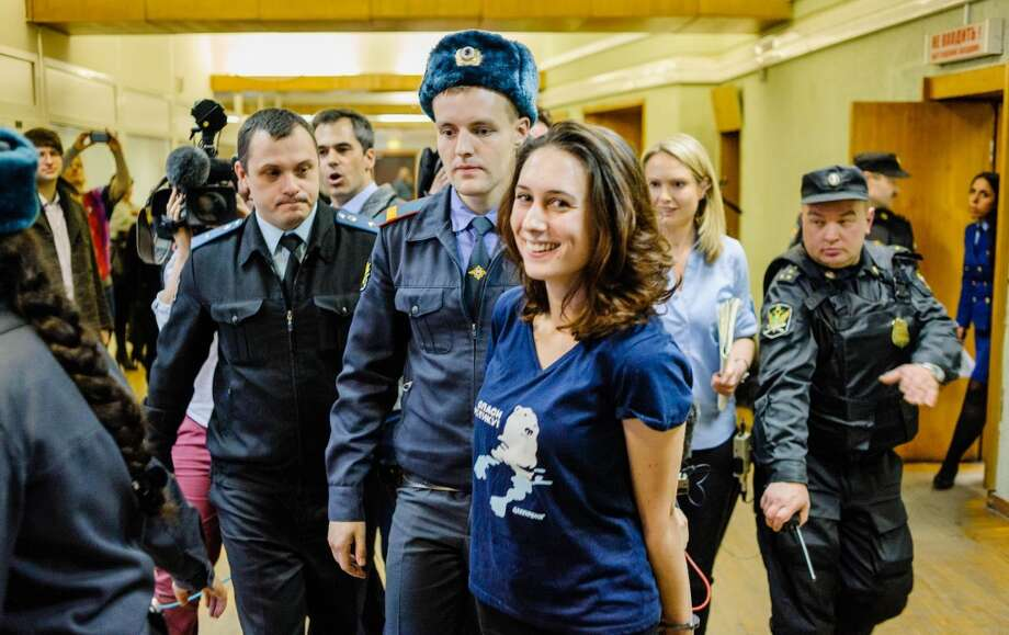 Greenpeace International activist Alexandra Harris (center), from the United Kingdom, arrives flanked by police at a hearing in Russia's second city of Saint Petersburg. Russian court granted bail Wednesday to three foreign Greenpeace activists who were detained for a protest against oil drilling, the first non-Russians to be set free from 30 people arrested over the action, the group said. Photo: VLADIMIR BARYSHEV, AFP/Getty Images