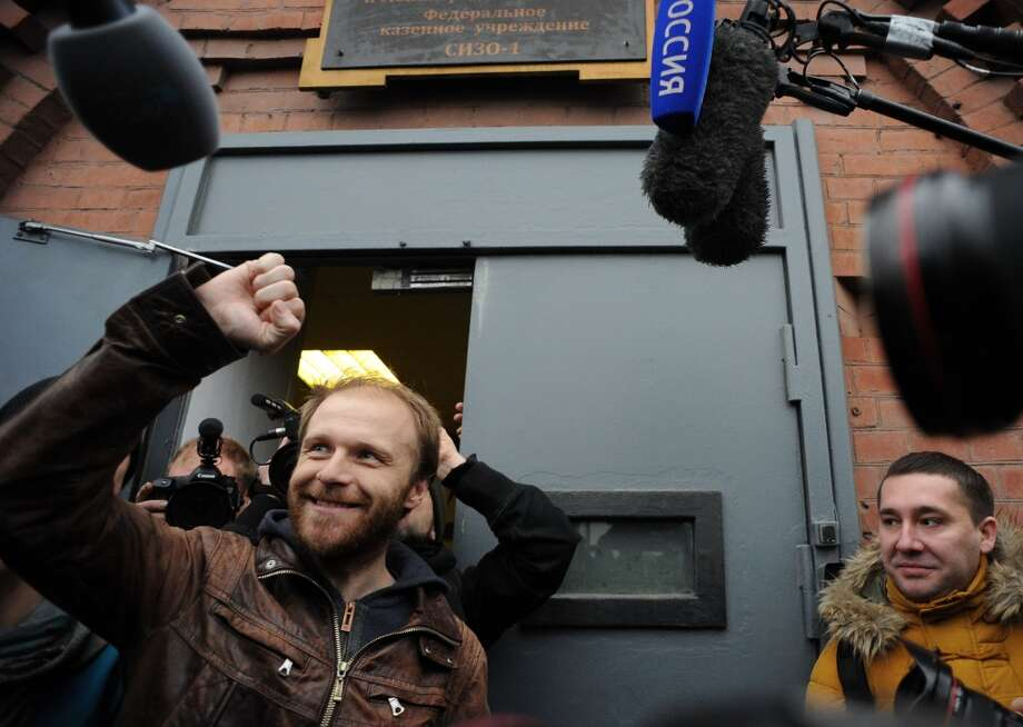 Russian photographer Denis Sinyakov raises his fist as he is released on bail from SIZO 1 detention centre in Saint Petersburg, on November 21, 2013. A Russian court granted bail to twenty arrested campaigners. Photo: OLGA MALTSEVA, AFP/Getty Images