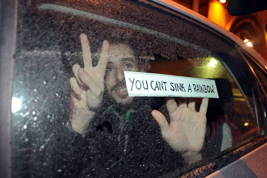 "Greenpeace International activist Cristian D'Alessandro makes the victory sign from inside a car while holding a sign reading ""You can't sink a rainbow"" as he leaves the SIZO 5 detention centre in Saint Petersburg after being released on bail on November 21, 2013. Photo: OLGA MALTSEVA, AFP/Getty Images"