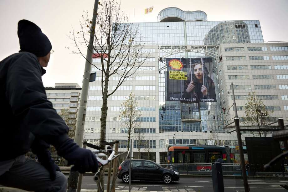 A cyclist looks at members of Greenpeace hanging a large poster of Dutch activist Faiza Oulahsen on the office building of Shell in Rotterdam on November 21, 2013. Russia arrested Oulahsen along with 29 other crew members of the Arctic Sunrise after activists in September scaled an oil rig in the Barents Sea owned by energy giant Gazprom. Photo: MARTIJN BEEKMAN, AFP/Getty Images