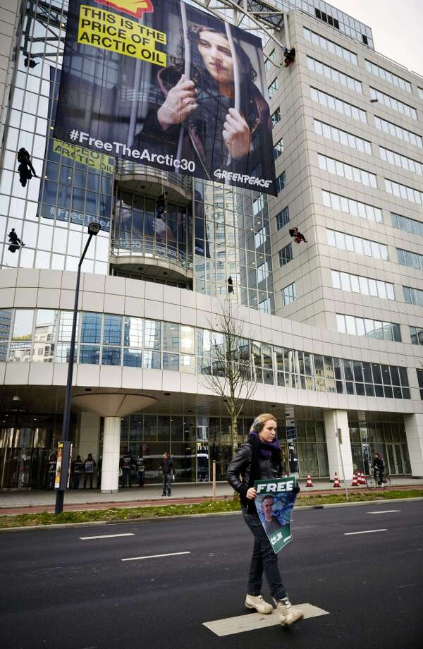 "Members of Greenpeace hang a large poster of Dutch activist Faiza Oulahsen on the office building of Shell during a protest calling for the release of the ""Arctic 30"" in Rotterdam on November 21, 2013. Russia arrested Oulahsen along with 29 other crew members of the Arctic Sunrise after activists in September scaled an oil rig in the Barents Sea owned by energy giant Gazprom. Photo: MARTIJN BEEKMAN, AFP/Getty Images"