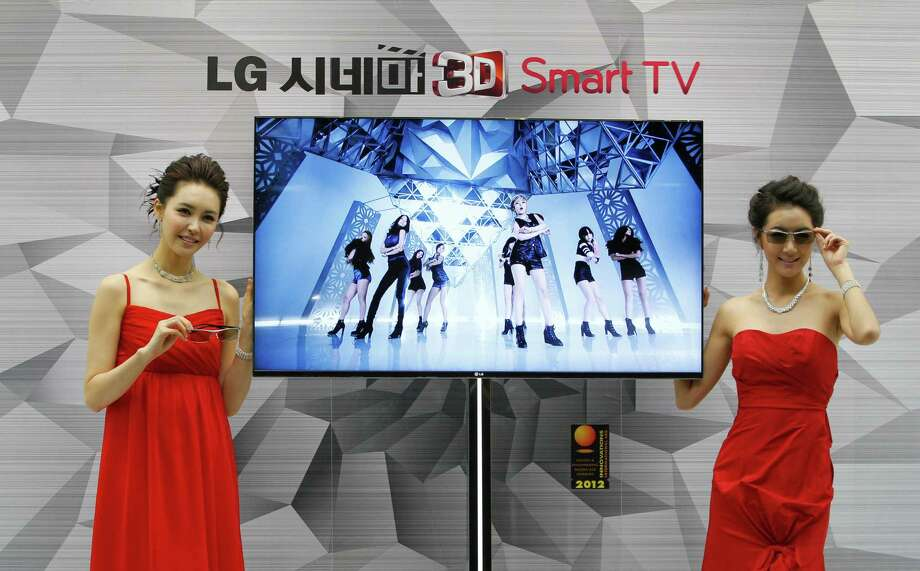 FILE - In this Thursday, Jan. 19, 2012 file photo, South Korean models pose with a CINEMA 3D Smart TV during a press conference to introduce the LG Electronics' television and the company's marketing strategy for 2012 in Seoul, South Korea. LG Electronics Inc. said it is investigating a claim that some of its smart TVs send information on home viewing habits back to the company without consent. The investigation comes after Jason Huntley, a 45-year-old IT consultant in Britain, detailed in his blog how his LG smart TV logged the channels he was watching and sent the data to LG. (AP Photo/Ahn Young-joon, File) ORG XMIT: TOK106 Photo: Ahn Young-joon / AP
