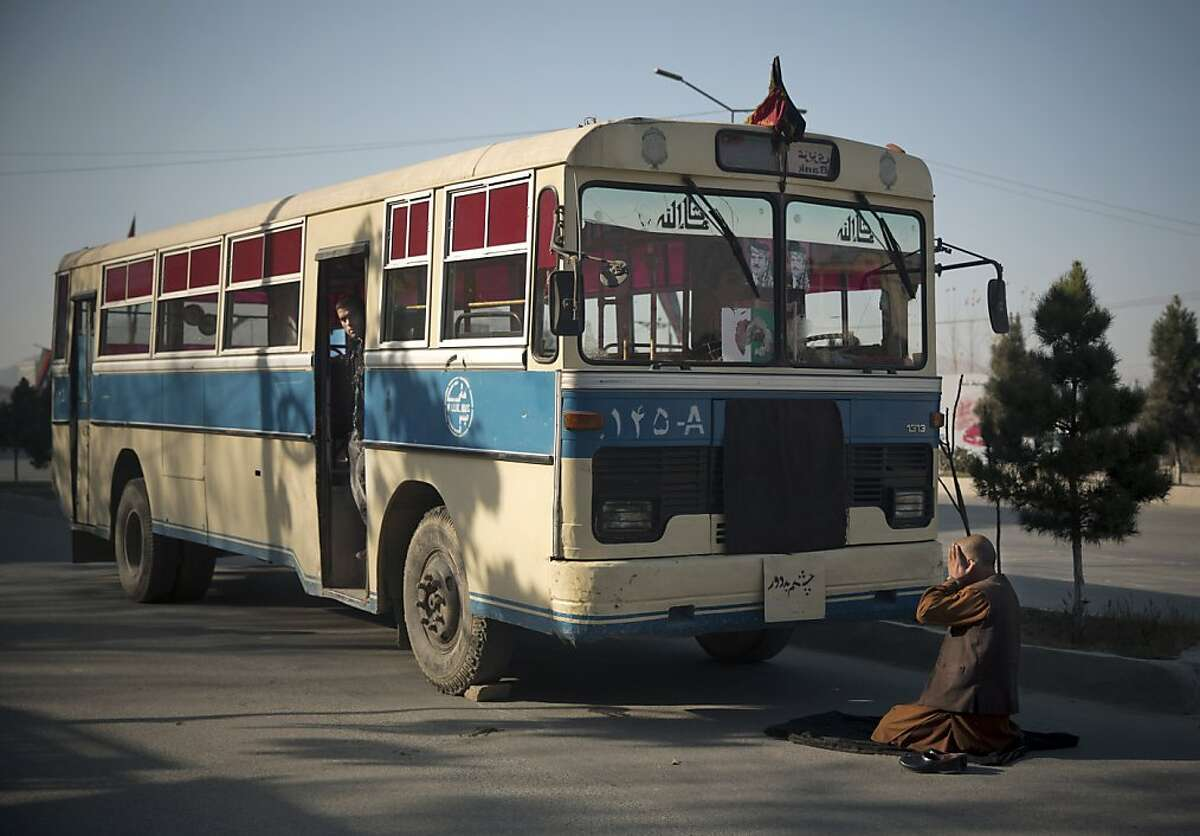 An Afghan bus driver offers prayers in front of his empty bus, as the center of Kabul came to a still stand, because thousands of prominent Afghans gathered to meet for a Loya Jirga to debate a contentious security agreement with the United States in the Afghan capital, Thursday, Nov. 21, 2013. Afghanistan's president Hamid Karzai said he backs a security deal with the United States but told the gathering of elders that if they and parliament approve the agreement it should be signed after next spring's elections. Without the agreement the United States previously warned that it will remove all its troops by the end of 2014. (AP Photo/Anja Niedringhaus)