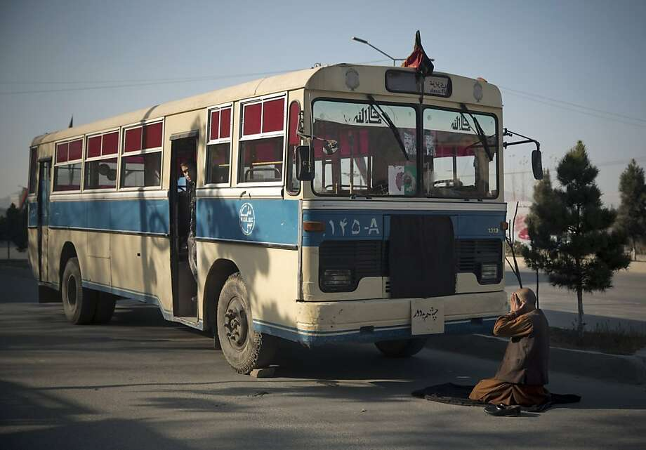 An Afghan bus driver offers prayers in front of his empty bus, as the center of Kabul came to a still stand, because thousands of prominent Afghans gathered to meet for a Loya Jirga to debate a contentious security agreement with the United States in the Afghan capital, Thursday, Nov. 21, 2013. Afghanistan's president Hamid Karzai said he backs a security deal with the United States but told the gathering of elders that if they and parliament approve the agreement it should be signed after next spring's elections. Without the agreement the United States previously warned that it will remove all its troops by the end of 2014.  (AP Photo/Anja Niedringhaus) Photo: Anja Niedringhaus, Associated Press