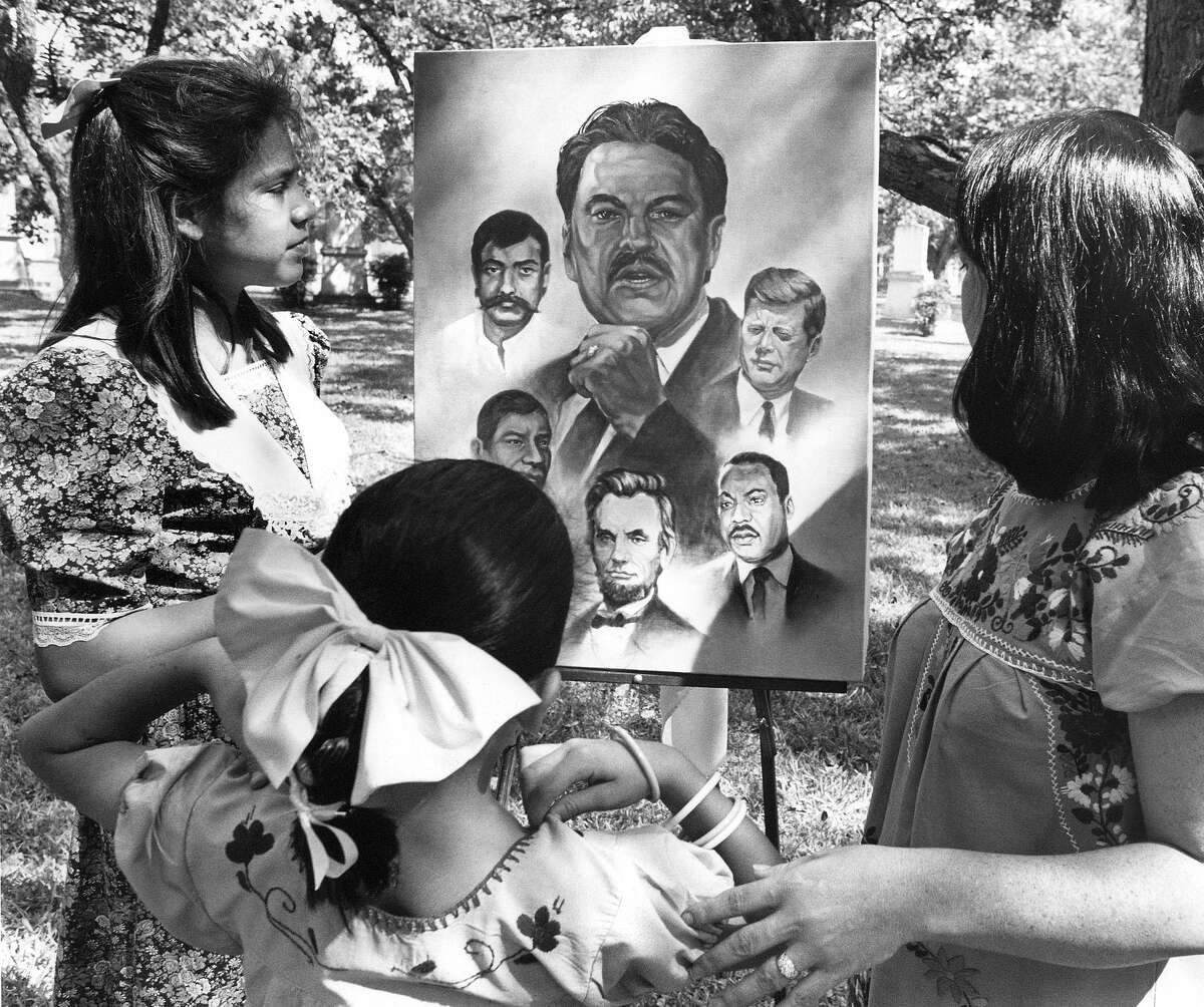Catarina Velásquez admires a painting of her father, Southwest Voter Registration Project founder Willie Velasquez, in a 1988 photo four months after his death.