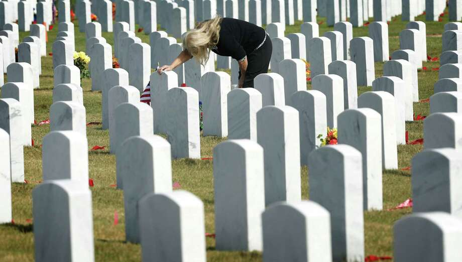 """Ingrid Evoy grieves over the grave of her husband, Army Veteran Joseph Evoy, after the Veterans Day Ceremony at Fort Sam Houston National Cemetery, Monday, Nov. 11, 2013. """"He was my life, and I miss him terribly,"""" she said of her spouse who died last year. Photo: San Antonio Express-News / © 2012 San Antonio Express-News"""
