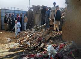 Muslim students stand in the rubble of an Islamic seminary that was hit by a suspected U.S. drone strike in Hangu district in Pakistan's Khyber Pakhtunkhwa province, Thursday, Nov. 21, 2013. A suspected U.S. drone carried out a rare missile strike in northwest Pakistan outside the country's remote tribal region on Thursday, killing some people, including three Afghan militants, Pakistani police and security officials said. (AP Photo/Abdul Basit)