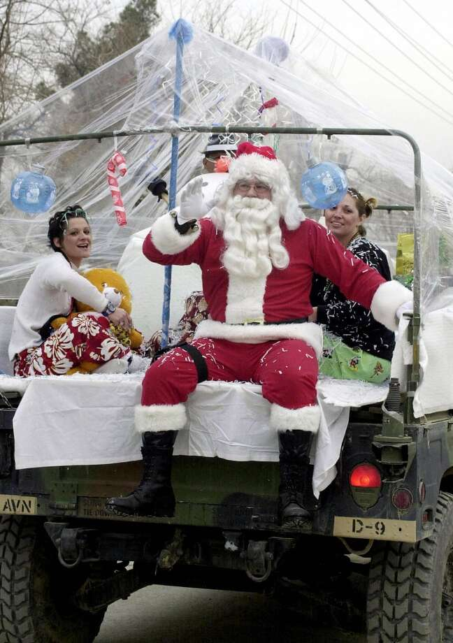 Bagram, AfghanistanSanta Claus waves from the back of a jeep to a Christmas Day parade of US soldiers in 2003. Photo: SHAH MARAI, AFP/Getty Images