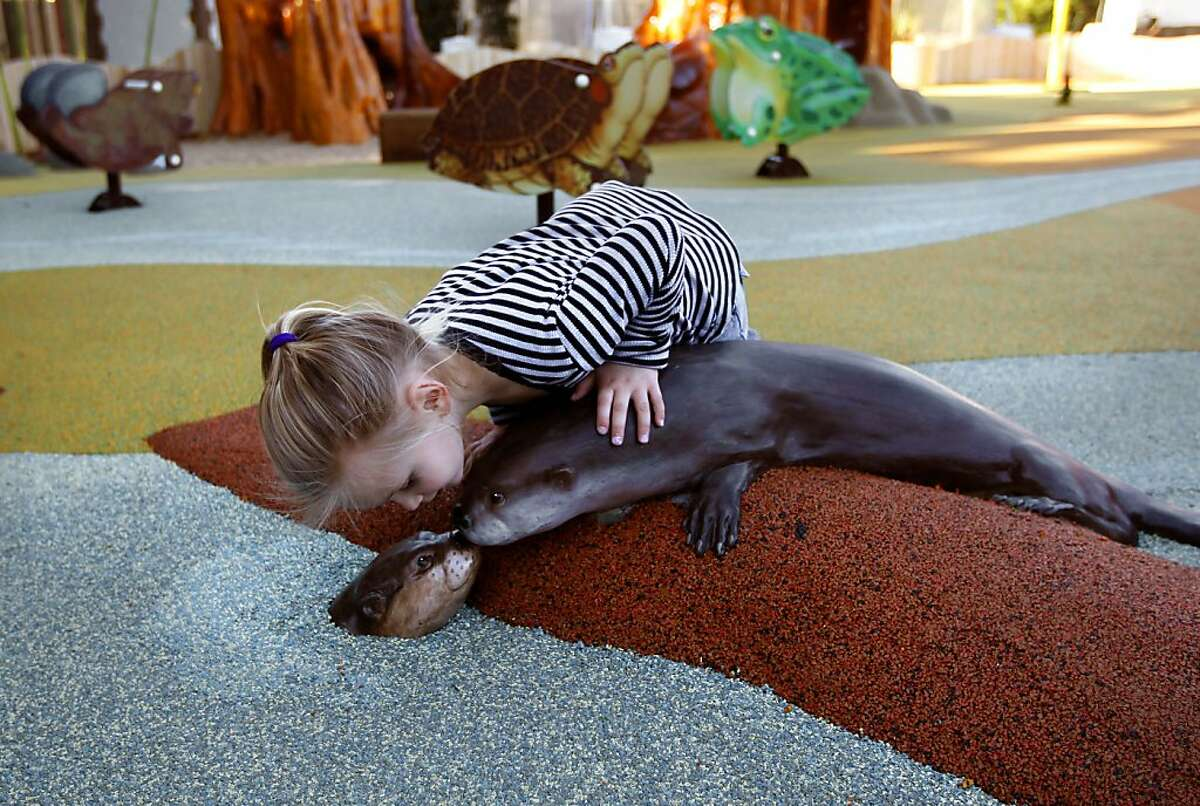 Megan Smith, 3, says hello to a model of an otter in the river play area for the youngest set as children try out the new kids' zone.