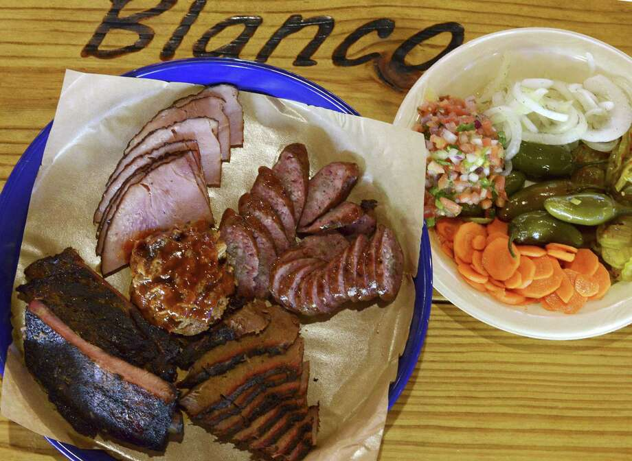 The house special plate offers a combination of brisket, ham, sausage and pork ribs, served with a choice of two sides and bread. Photo: Photos By Billy Calzada / San Antonio Express-News