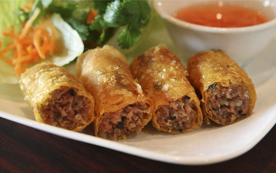 Vietnamese egg rolls have a meaty filling and are accompanied with a dipping sauce and lettuce and herbs.