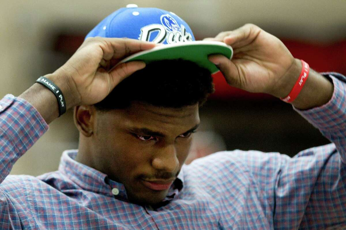 St. John's senior Justice Winslow places a Duke hat on his head as he announces his decision to play basketball at the North Carolina school Thursday, Nov. 21, 2013, in Houston.