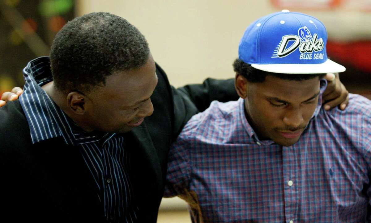 St. John's senior Justice Winslow is embraced by his father, Rickie Winslow, after announcing his decision to play basketball at Duke Thursday, Nov. 21, 2013, in Houston.