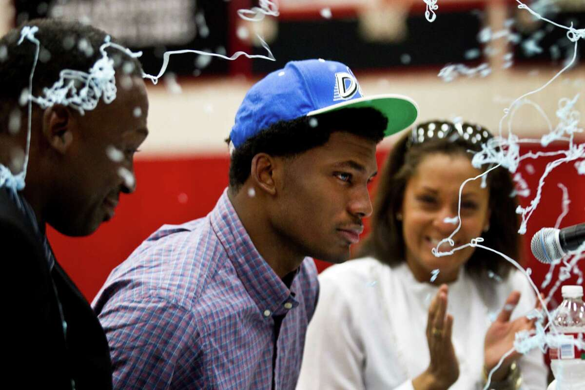 Silly string flies as St. John's senior Justice Winslow announces his decision to play basketball at Duke Thursday, Nov. 21, 2013, in Houston. Winslow is flanked by his parents, Rickie Winslow, left, and mother Robin Davis, right.