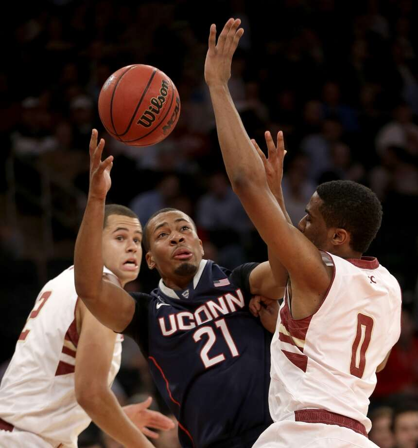 Connecticut's Omar Calhoun, center, fights for control of the ball with Boston College's Garland Owens, right, and Ryan Anderson during the first half of an NCAA college basketball game on Thursday, Nov. 21, 2013, in New York. Photo: AP Photo/Seth Wenig
