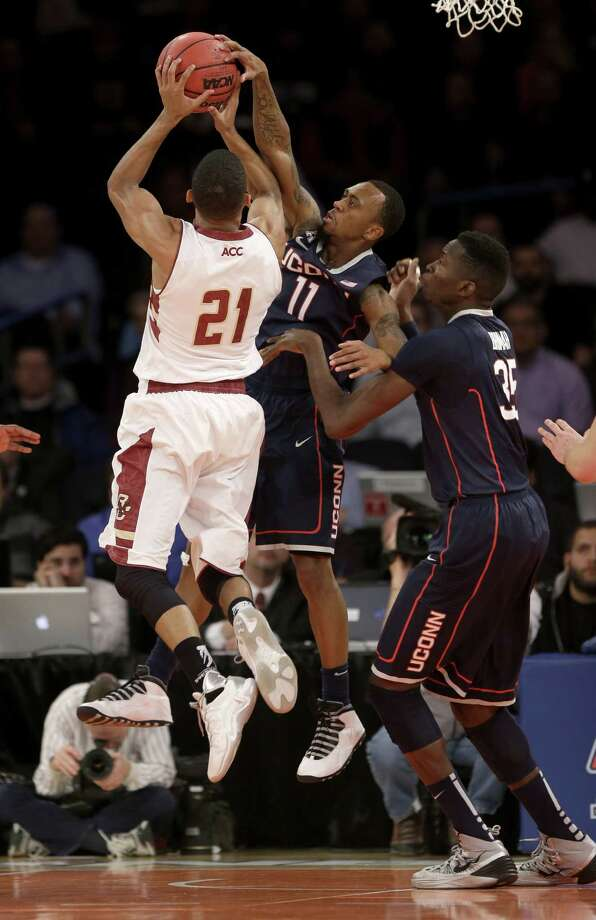 Connecticut's Ryan Boatright, center, gets his hand on a shot by Boston College's Olivier Hanlan, left, while Amida Brimah looks on during the first half of an NCAA college basketball game on Thursday, Nov. 21, 2013, in New York. Photo: Seth Wenig, AP / Associated Press