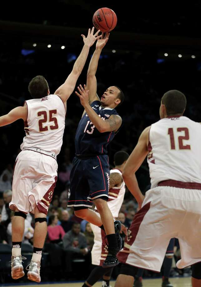 Connecticut's Shabazz Napier, center, shoots over Boston College's Joe Rahon, left, during the first half of an NCAA college basketball game on Thursday, Nov. 21, 2013, in New York. Photo: Seth Wenig, AP / Associated Press