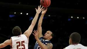 Connecticut's Shabazz Napier, center, shoots over Boston College's Joe Rahon, left, during the first half of an NCAA college basketball game on Thursday, Nov. 21, 2013, in New York.