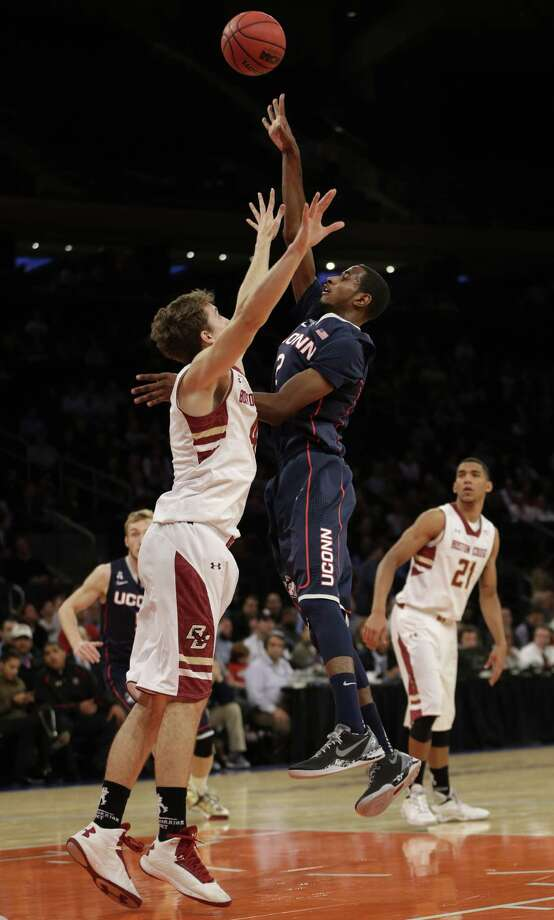 Connecticut's DeAndre Daniels, center, shoots over Boston College's Eddie Odio, left, while Olivier Hanlan looks on during the first half of an NCAA college basketball game Thursday, Nov. 21, 2013, in New York. Photo: Seth Wenig, AP / Associated Press