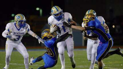 Newtown's Cooper Gold, 11, is tackled by Brookfield's Benjamin Martone, 20, and Peter Manesis, 10 during the SWC football championship game between Newtown and Brookfield high schools in Brookfield, Conn, on Thursday night, November 21, 2013.