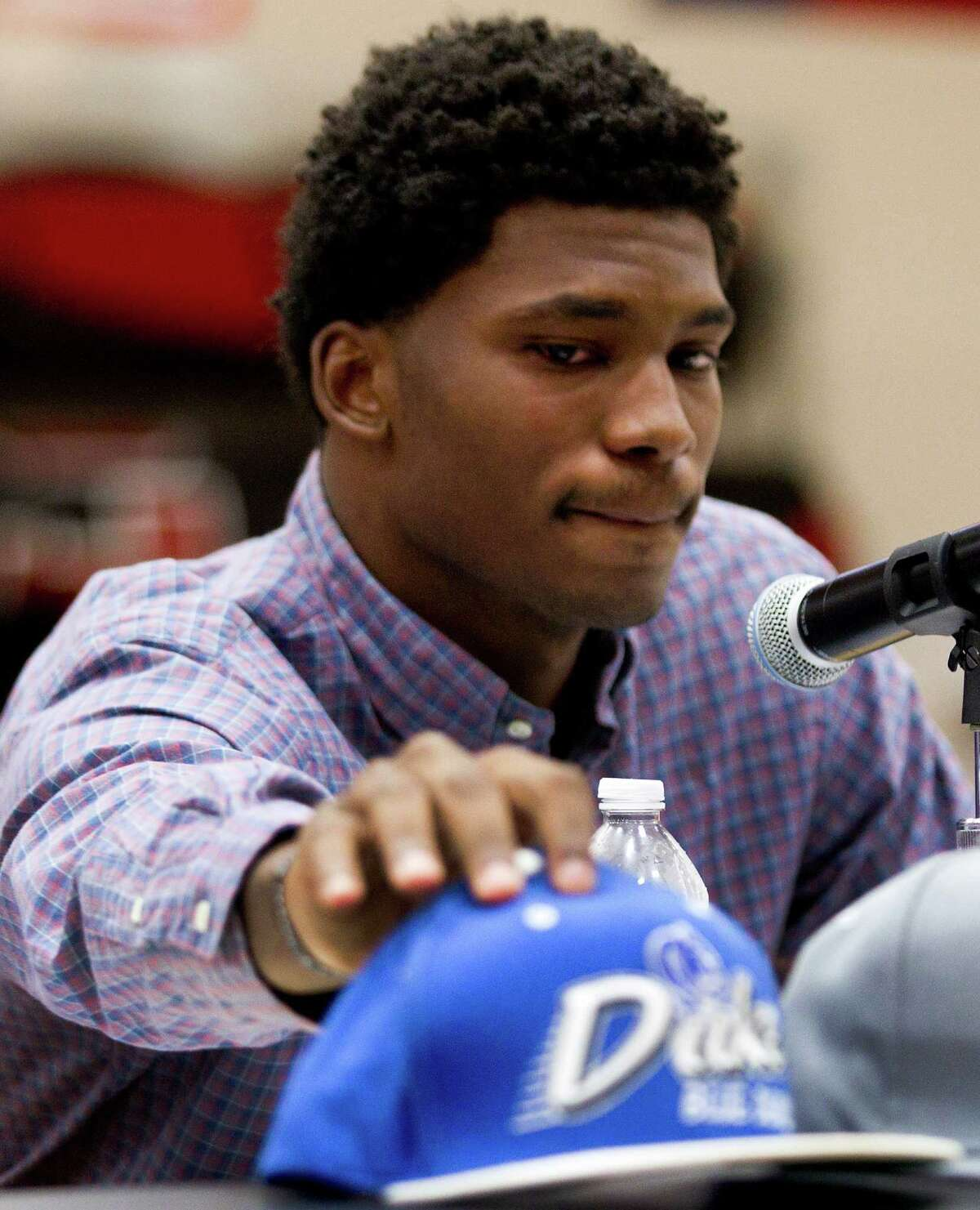 St. John's senior Justice Winslow reaches to pick up a Duke hat announces his decision to play basketball at the North Carolina school Thursday, Nov. 21, 2013, in Houston. ( Brett Coomer / Houston Chronicle )