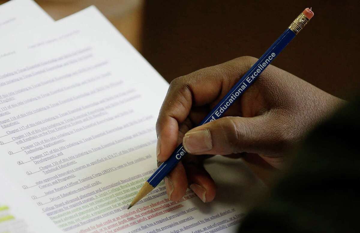 Texas Board of Education member Lawrence A. Allen Jr. uses a pencil to to mark and follow proposals related to algebra II, Thursday, Nov. 21, 2013, in Austin, Texas. The Board of Education is casting critical votes on new science textbooks for use statewide, and on whether algebra II should be a required high school course.(AP Photo/Eric Gay)