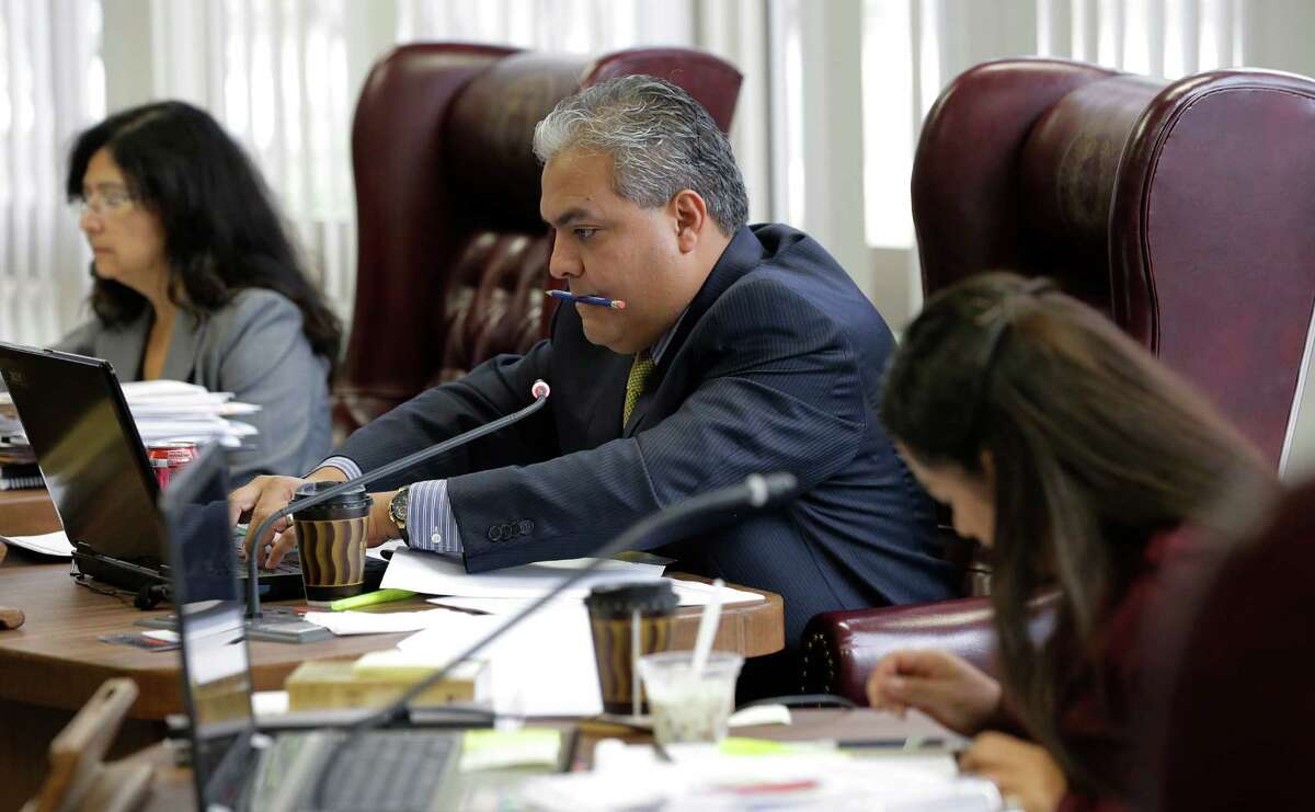 Texas Board of Education member Ruben Cortez Jr., center, takes part in meetings, Thursday, Nov. 21, 2013, in Austin, Texas. The Board of Education is casting critical votes on new science textbooks for use statewide, and on whether algebra II should be a required high school course.(AP Photo/Eric Gay)