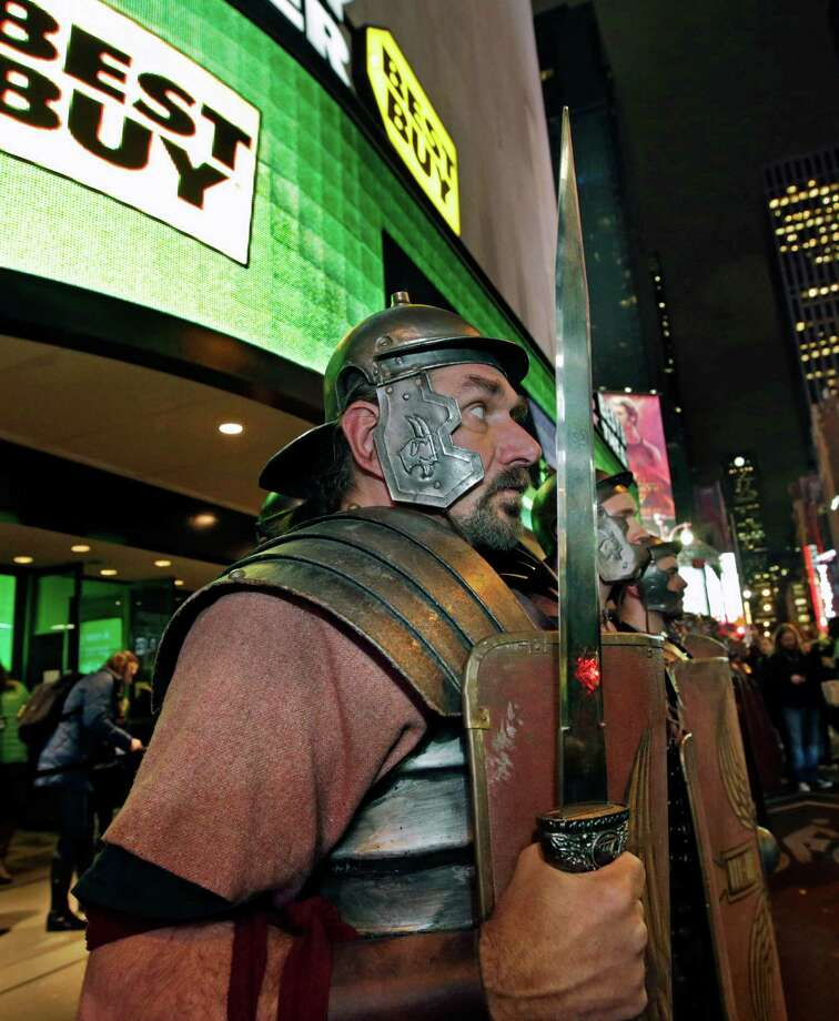 Xbox characters dressed as Roman soldiers stand at attention outside the Best Buy Theater in Times Square after arriving in advance of the midnight launch of  Microsoft's Xbox One video game console, Thursday, Nov. 21, 2013, in New York. (AP Photo/Kathy Willens) Photo: Kathy Willens, Getty Images / AP