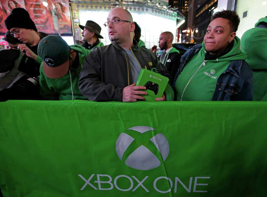 People line up outside the Best Buy Theater in Times Square awaiting the opportunity to purchase Microsoft's Xbox One video gaming console at a midnight sales launch, Thursday, Nov. 21, 2013, in New York. (AP Photo/Kathy Willens) Photo: Kathy Willens, Getty Images / AP
