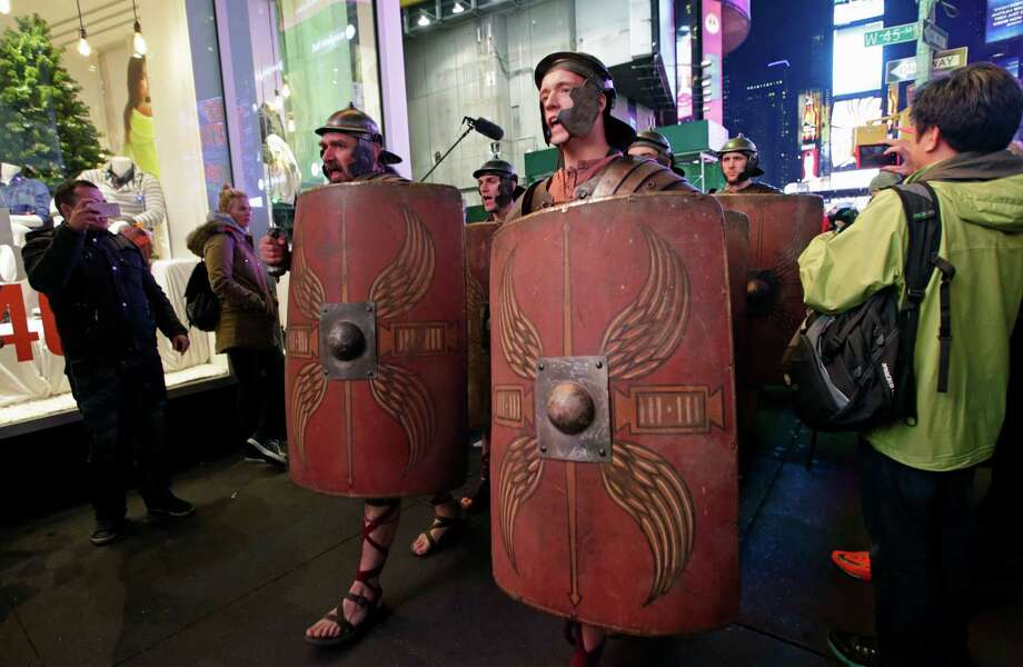 Tourists snap pictures of Xbox characters dressed as Roman soldiers as the soldiers parade through Times Square in advance of the midnight sales launch of Microsoft's Xbox One video gaming console, Thursday, Nov. 21, 2013, in New York. (AP Photo/Kathy Willens) Photo: Kathy Willens, Getty Images / AP