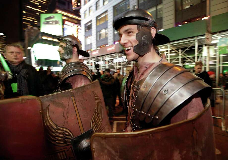 Pedestrians watch as Xbox characters dressed as Roman soldiers parade through Times Square before arrive at the Best Buy Theater in advance of the midnight sales launch of Microsoft's Xbox One video gaming console, Thursday, Nov. 21, 2013, in New York. (AP Photo/Kathy Willens) Photo: Kathy Willens, Getty Images / AP