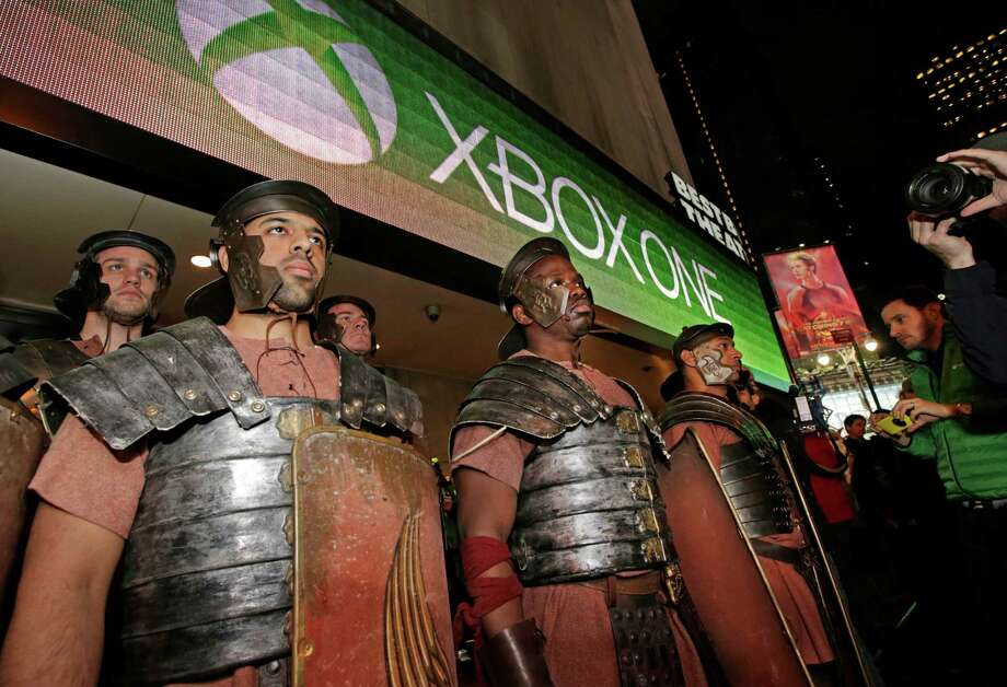 Xbox characters dressed as Roman soldiers stand at attention outside the Best Buy Theater in Times Square in advance of the midnight sales launch of Microsoft's  Xbox One video game console, Thursday, Nov. 21, 2013, in New York. (AP Photo/Kathy Willens) Photo: Kathy Willens, Getty Images / AP