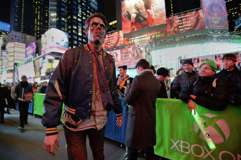 A man dressed as a zombie as part of Microsoft's Xbox One game console launch event November 21, 2013 walks past people waiting in line for the launch concert outside the Best Buy Theater in New York's Times Square. The Xbox One officially goes on sale at 12:01 am EST November 22. AFP PHOTO/Stan HONDASTAN HONDA/AFP/Getty Images Photo: STAN HONDA, Getty Images / AFP