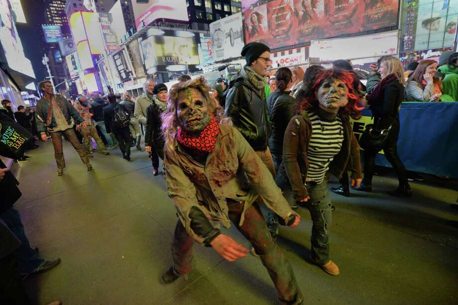People dressed as zombies, part of Microsoft's Xbox One game console launch event November 21, 2013 walk outside the Best Buy Theater in New York's Times Square. The Xbox One officially goes on sale at 12:01 am EST November 22. AFP PHOTO/Stan HONDASTAN HONDA/AFP/Getty Images Photo: STAN HONDA, Getty Images / AFP