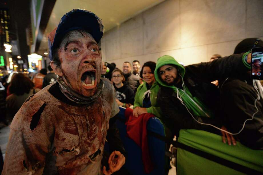 A man dressed as a zombie performs during in the Microsoft's Xbox One game console launch event November 21, 2013 outside the Best Buy Theater in New York's Times Square. The Xbox One officially goes on sale at 12:01 am EST November 22. AFP PHOTO/Stan HONDASTAN HONDA/AFP/Getty Images Photo: STAN HONDA, Getty Images / AFP