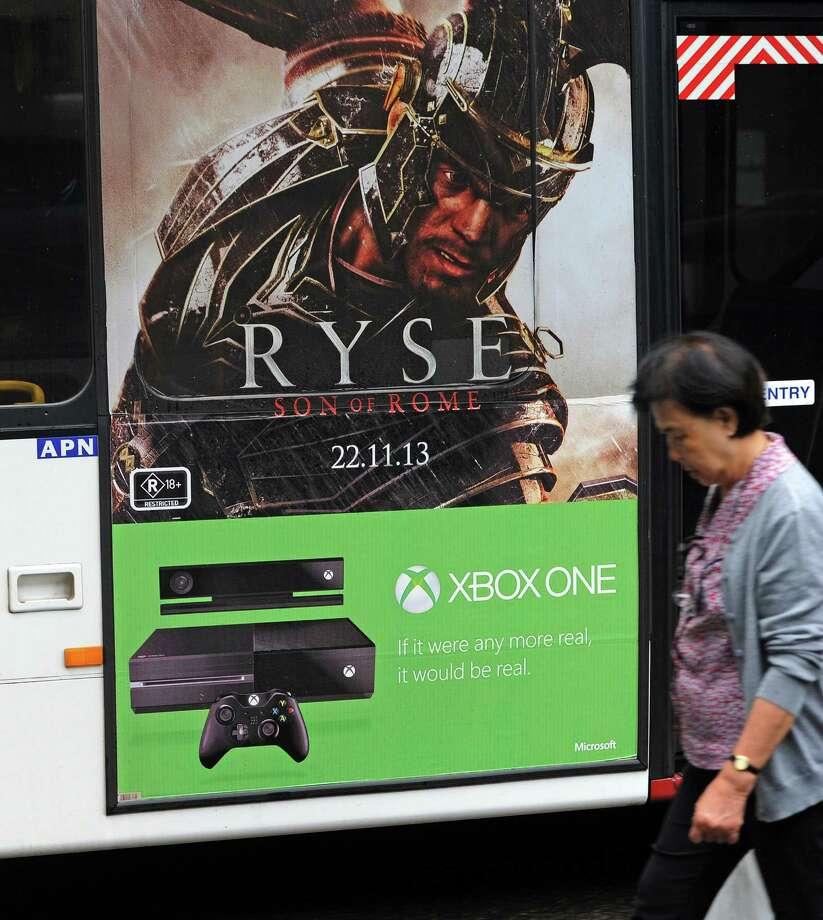 A woman (R) walks past a commuter bus displaying signage advertising the new microsoft Xbox One console in Sydney on November 22, 2013. Microsoft on November 22 releases its Xbox One game console, taking on Sony's PlayStation 4 in a battle for the hearts and minds of Internet-era home entertainment.       AFP PHOTO / Greg WOODGREG WOOD/AFP/Getty Images Photo: GREG WOOD, Getty Images / AFP