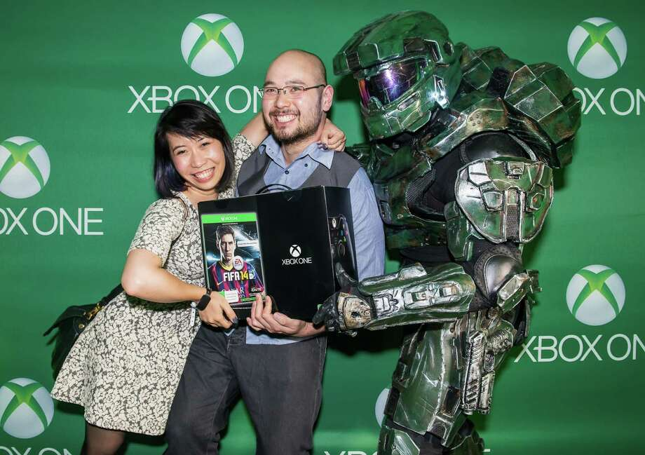 This handout photo taken late on November 21, 2013 and released by Microsoft shows Francis King (C) and Angela Tran (L), the first people in Australia to collect their Xbox One upon its release at a launch party in Sydney.  Microsoft on November 22, 2013 releases its Xbox One game console, taking on Sony's PlayStation 4 in a battle for the hearts and minds of Internet-era home entertainment.     AFP PHOTO / MICROSOFT