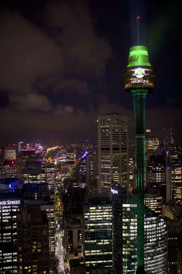 This handout photo taken on November 21, 2013 and released by Microsoft shows the Sydney Tower (R) lit up in green during the Xbox One launch.  Microsoft on November 22, 2013 releases its Xbox One game console, taking on Sony's PlayStation 4 in a battle for the hearts and minds of Internet-era home entertainment.     AFP PHOTO / MICROSOFT