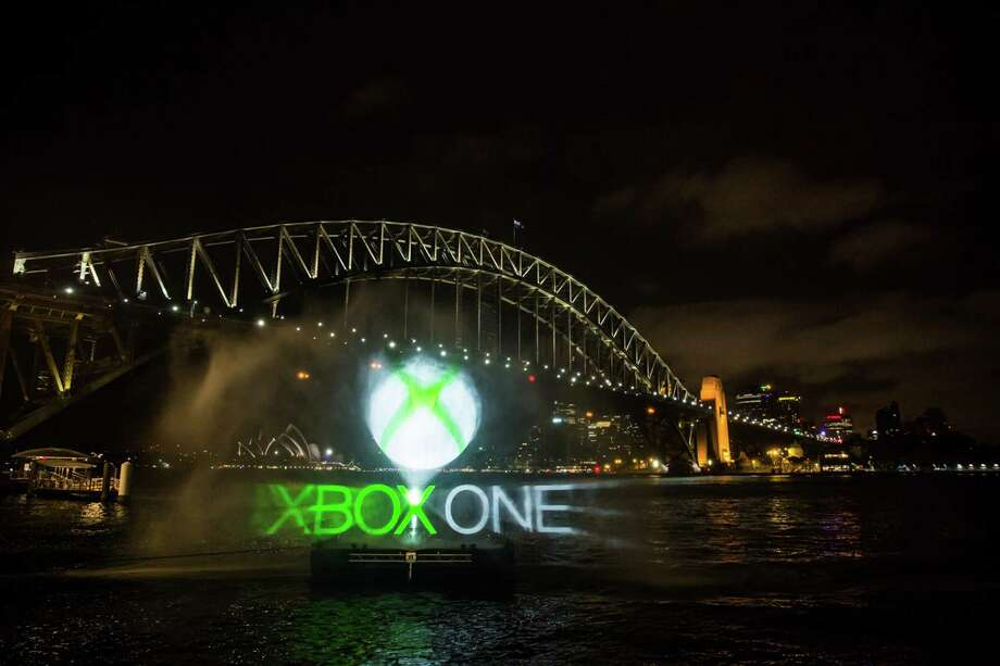 This handout photo taken on November 21, 2013 and released by Microsoft shows an Xbox One 3D water projection (C) taking place on Sydney Harbour beneath the North Pylon of the Sydney Harbour Bridge. Microsoft on November 22, 2013 releases its Xbox One game console, taking on Sony's PlayStation 4 in a battle for the hearts and minds of Internet-era home entertainment.     AFP PHOTO / MICROSOFT