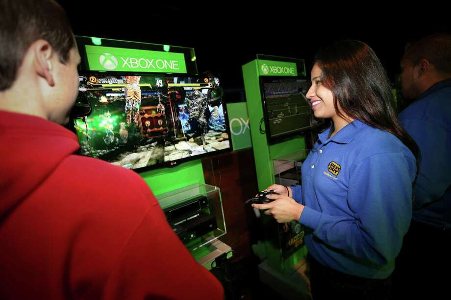 IN THIS IMAGE DISTRIBUTED BY AP IMAGES FOR BEST BUY - Best Buy Blue Shirt Zasha Lucas, right, and a gamer play the new Xbox One on launch night at Best Buy Theater, Thursday, Nov. 21, 2013, in New York. (John Minchillo / AP Images for Best Buy) Photo: John Minchillo, Getty Images / AP Images