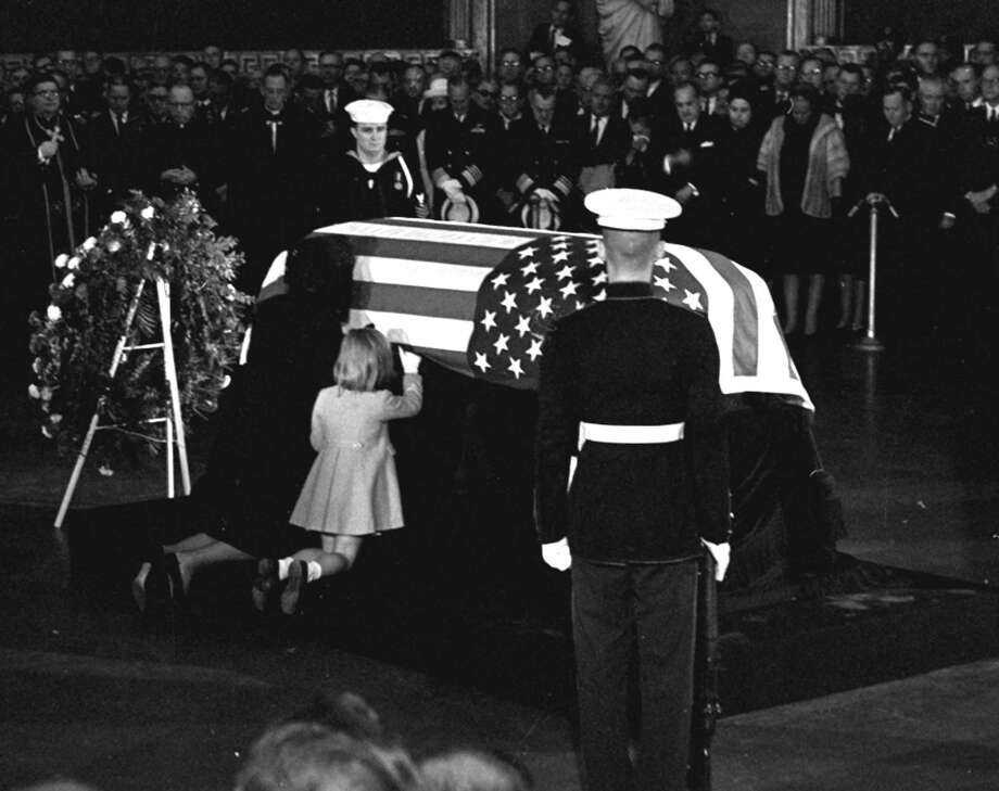 A file photo taken on Nov. 24, 1963, shows Jacqueline Kennedy kissing the casket of her husband, President John F. Kennedy, as his body lies in state in the rotunda of the U.S. Capitol in Washington. Their daughter, Caroline, kneels next to the coffin. Photo: Henry L. Griffin, Associated Press / AP Photo