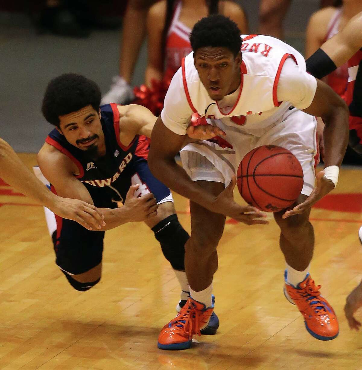Houston's Danrad Knowles, right, fights for a loose ball against Howard's Ausar Madison during the second half of an NCAA college basketball game, Thursday, November 21, 2013, at Hofheinz Pavilion in Houston.