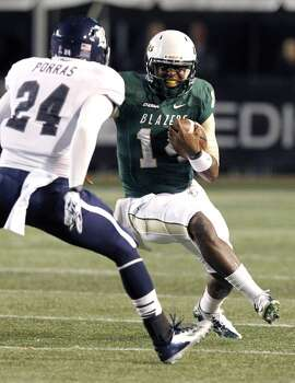 UAB quarterback Jonathan Perry (14) tries to get around Rice safety Paul Porras (24). Photo: Butch Dill, Associated Press