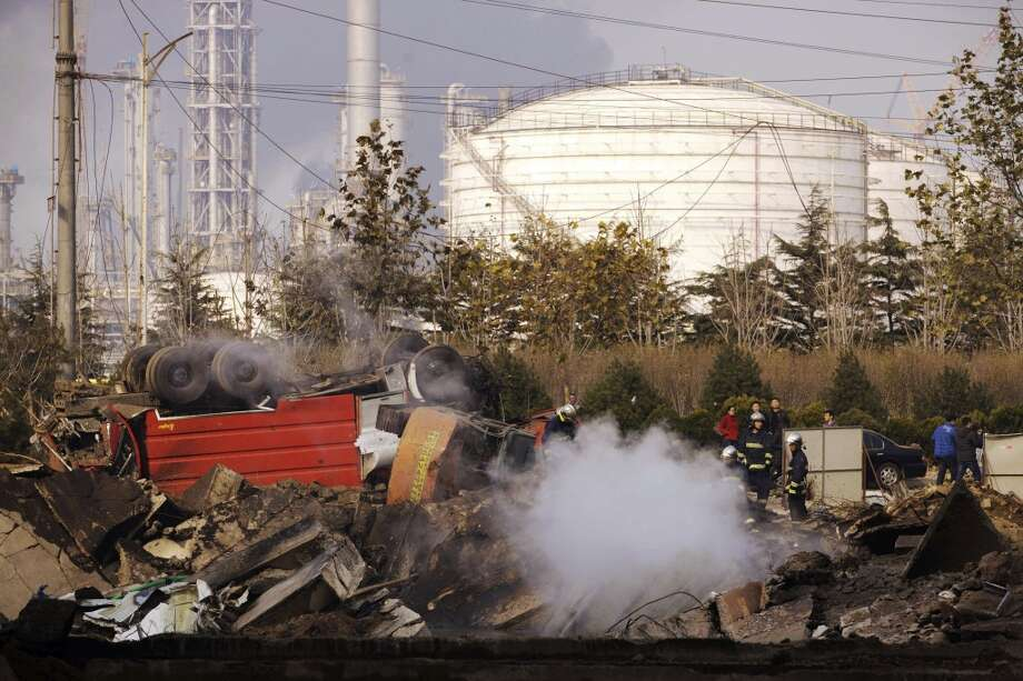 Firefighters work on a damaged site following a pipeline explosion in Qingdao in east China's Shandong province Friday, Nov. 22, 2013. Leaked oil from a ruptured oil pipe, owned by China's largest oil refiner, Sinopec, caught fire and exploded Friday in an eastern Chinese port city, killing and injuring many people. Photo: AP