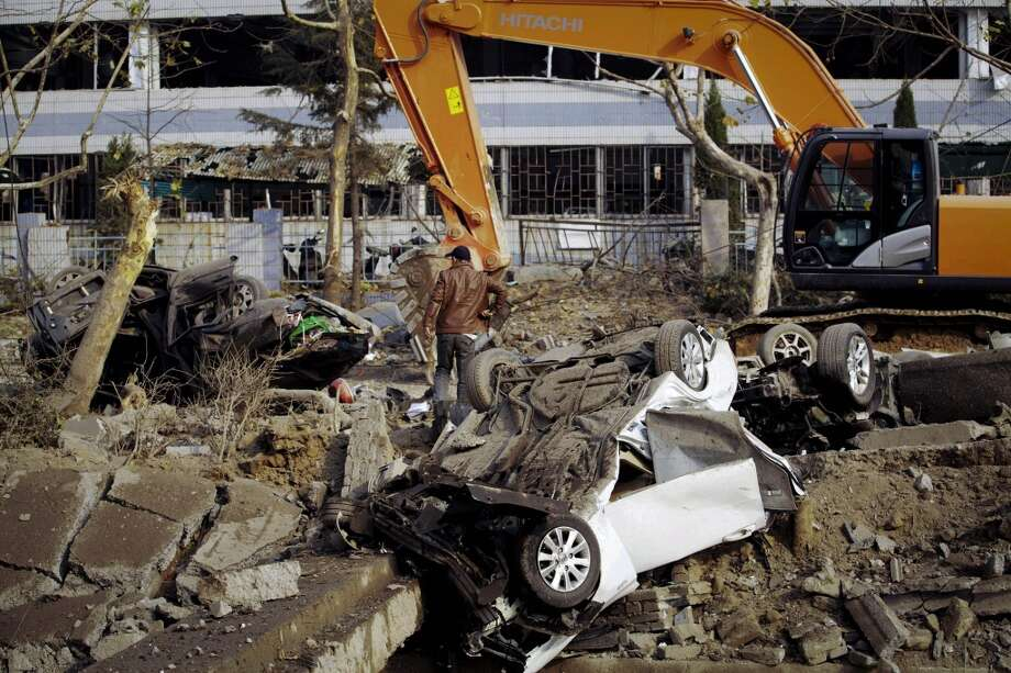 A man walks past damaged vehicles following a pipeline explosion in Qingdao in east China's Shandong province Friday, Nov. 22, 2013. Leaked oil from a ruptured oil pipe, owned by China's largest oil refiner, Sinopec, caught fire and exploded Friday in an eastern Chinese port city, killing and injuring many people. Photo: Uncredited, ASSOCIATED PRESS