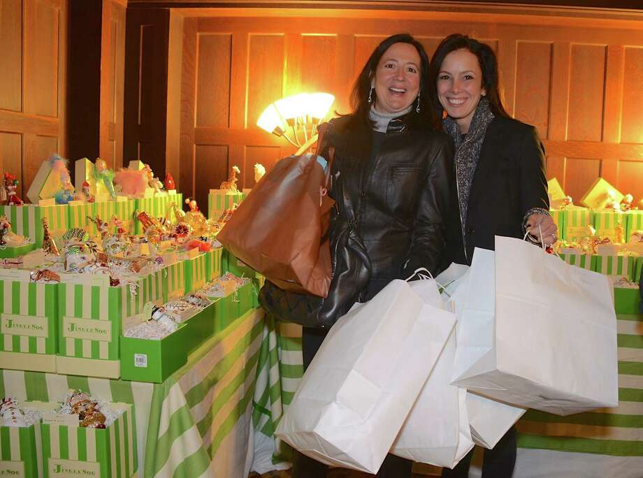 Shoppers Roseanne Conheeny and Tina Kramer have their hands full at the Young Women's League Holiday Market Preview Party at Waveny House on November 20, 2013 in New Canaan, Conn. Photo: Jeanna Petersen Shepard / New Canaan News Freelance