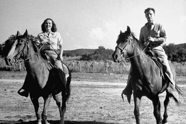 Mr. and Mrs. Glenn McCarthy riding horses.